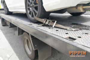 car secured on flatbed tow truck