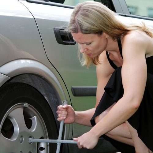 A Picture of a Woman in a Black Dress Changing a Tire.